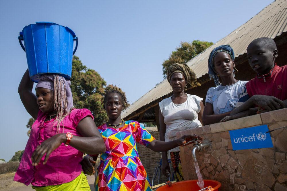 Dorfbewohner holen Wasser am Bohrloch im abgelegenen Dorf Dara, Guinea-Bissau. Unicef hat Wassertanks sowie Sonnenkollektoren installiert, um die Klinik mit fließendem Wasser und Strom zu versorgen.