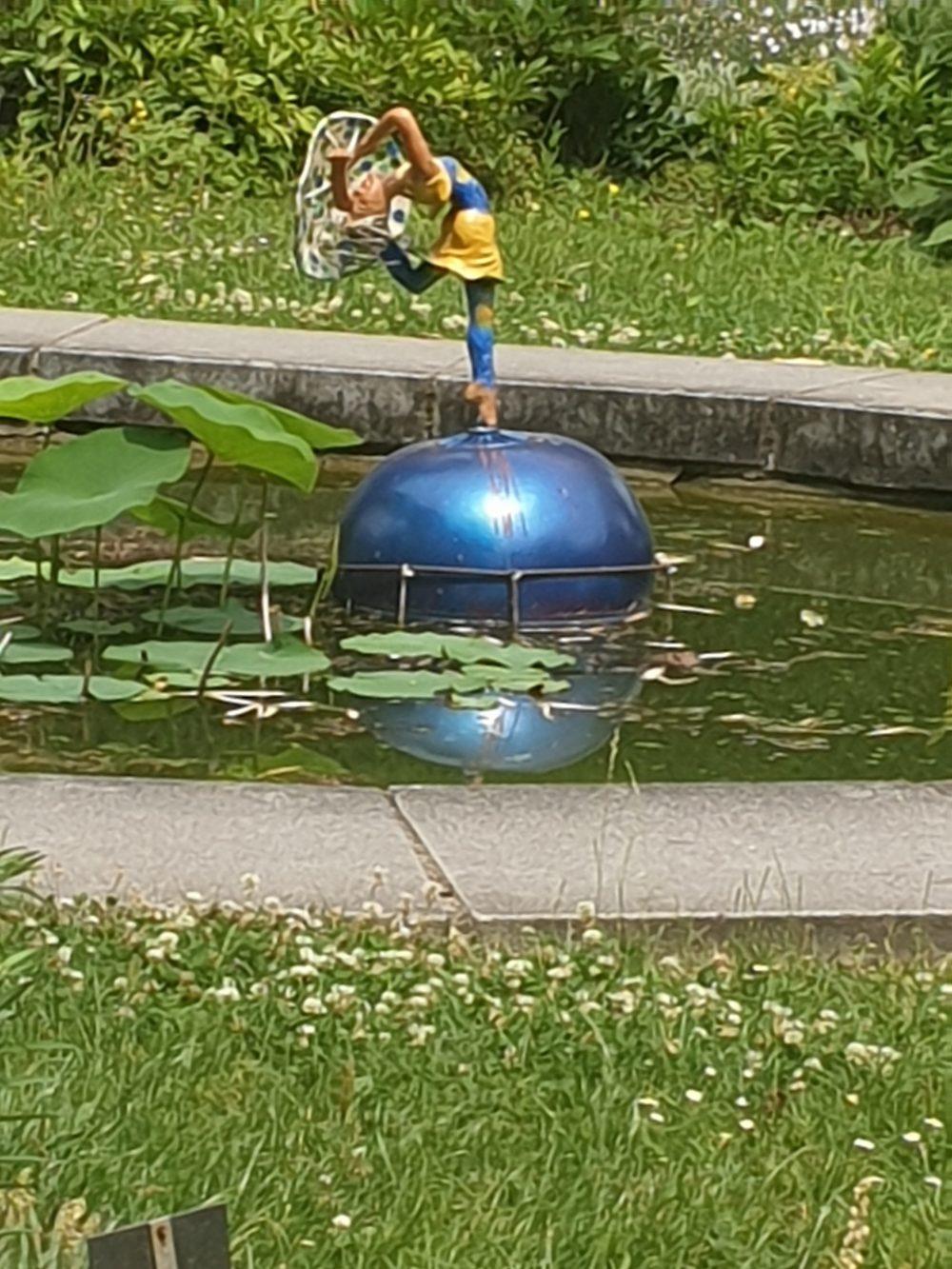 Kleine Figur einer Tänerzin auf einer Kugel im Teich