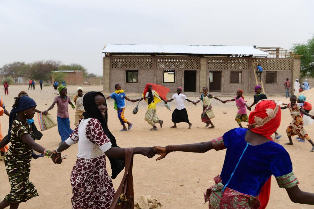Kinder spielen auf dem Spielplatz ihrer Schule. Im Hintergrund der Bau von zwei Klassenzimmern aus Recycling-Material, u.a. Plastikflaschen in Gaoui, einem Vorort von Ndjamena, der Hauptstadt des Tschad