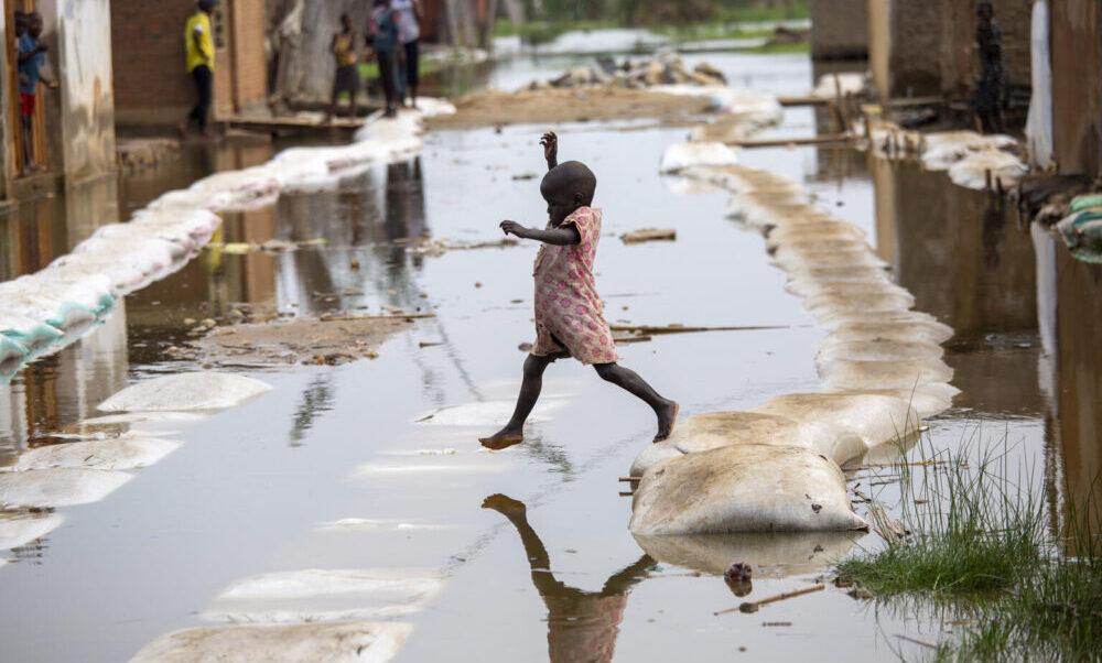 Am 4. März 2021 spielt ein Kind in den Fluten von Gatumba in der Nähe von Bujumbura in Burundi. Mindestens 50.000 Menschen waren im vergangenen Jahr von den Überschwemmungen in der Region betroffen.