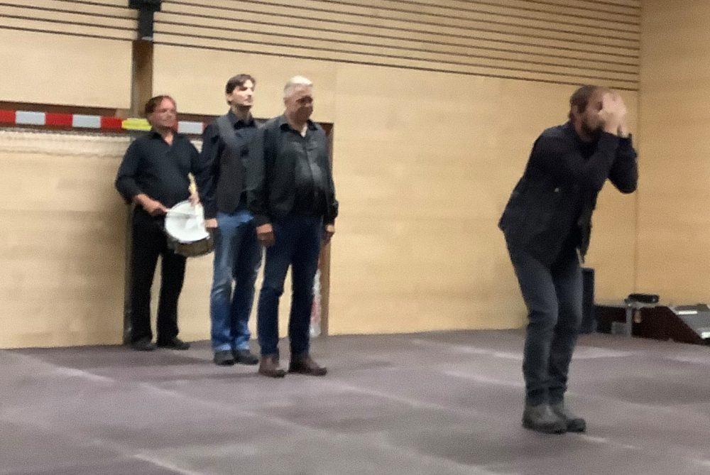 Szenenfoto - vier Männer in einer Schlange hintereinander