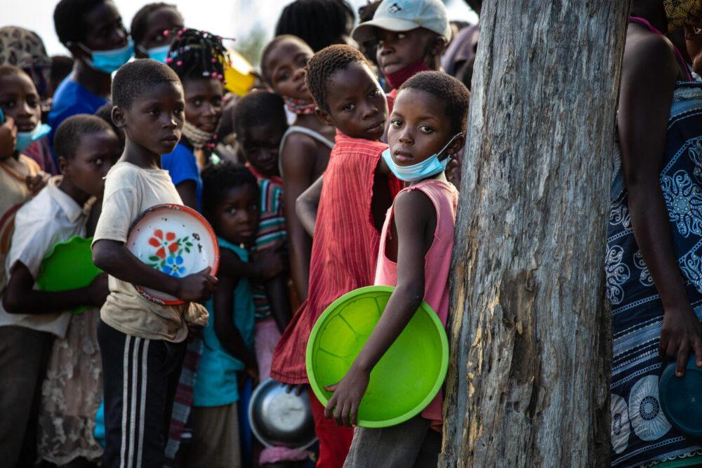 Am 24. Januar 2021 trägt ein Kind in der Provinz Sofala, Mosambik, eine leere Schüssel und steht während einer Essensverteilung im Tica Relocation Center, 80 Kilometer von der Stadt Beira entfernt, in einer Schlange. Vom tropischen Wirbelsturm Eloise betroffene Familien sind aus den umliegenden Vierteln hierher gezogen, um Schutz und Hilfe zu suchen.
