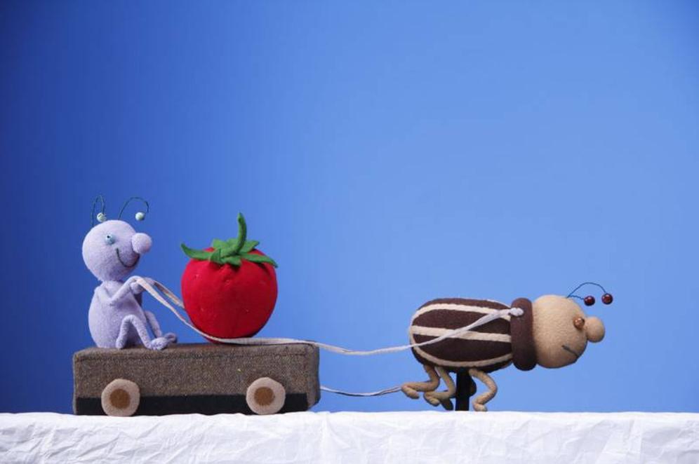 Käferartige Puppen und eine große Stoff-Erdbeere auf einem Schlitten aus dem Figurentheaterstück