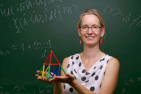 Physik-Uni-Professorin mit Modell aus Streben und vor einer Tafel mit Formeln
