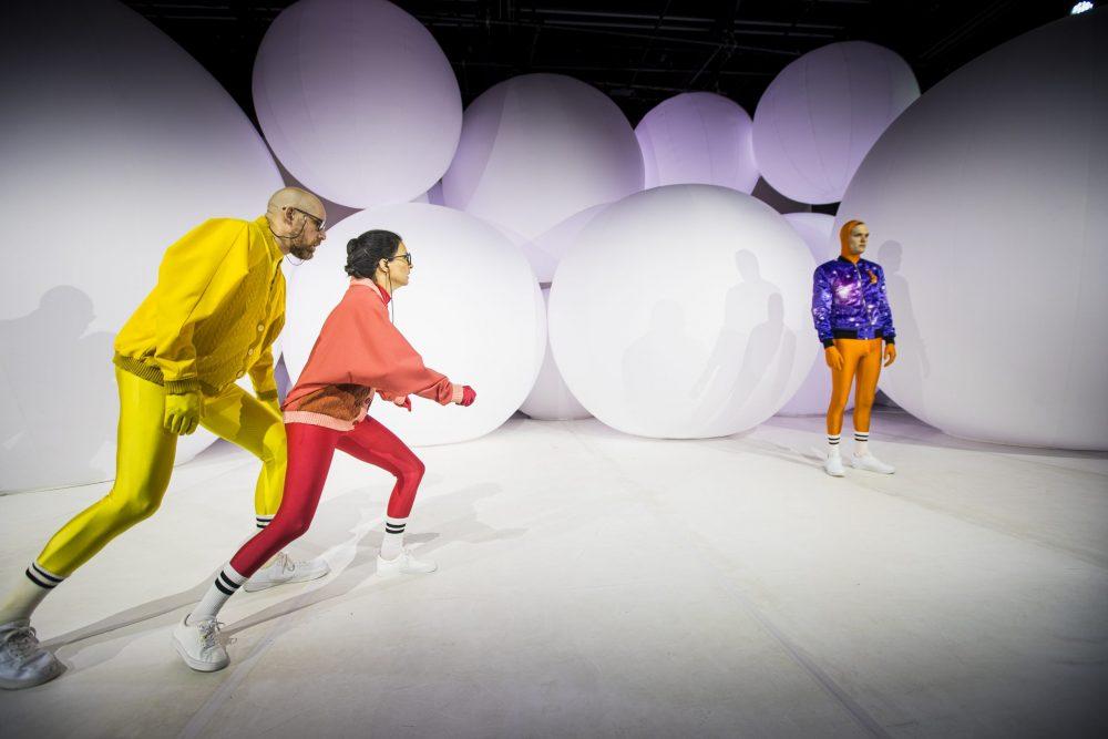 """Szenenfoto aus """"Rand"""" - jeweils Schauspieler*innen in bunten, knalligen Sportanzügen vor oder zwischen riesigen weißen, ständig aufgeblasenen Ballons"""