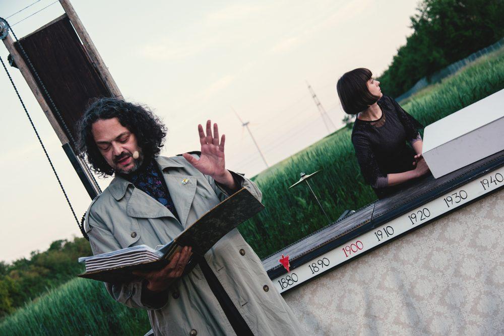 Mann mit dicker Mappe - Schauspieler Martin Brachvogel - vor einer kleinen Bühne, dahinter Frau vor einem Weizenfeld - Schauspielerin Nora Winkler