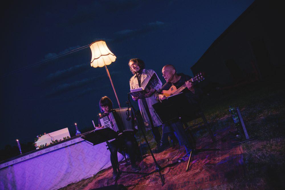 Nora Winkler am Akkordeon, Martin Brachvogel mit dicker Mappe und Robert Lepenik an der Gitarre vor der kleinen Bühne mit Kartonhaus-Modell