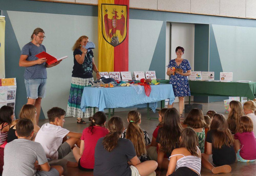 Kinder sitzen im Kreis, Erwachsene lesen vor