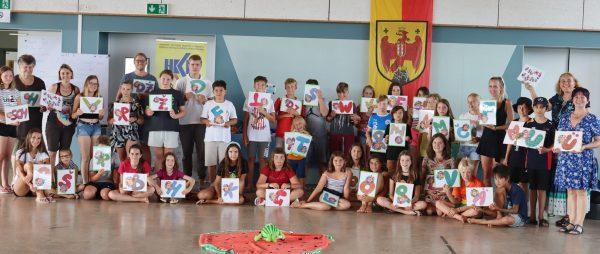 Kinder stehen und zeigen Zeichnungen und Buchstaben
