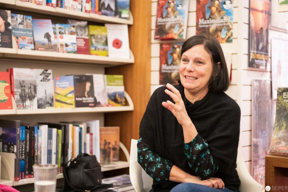 Die Illustratorin und Autorin Linda Wolfsgruber sitzt neben einem Regal mit vielen Büchern