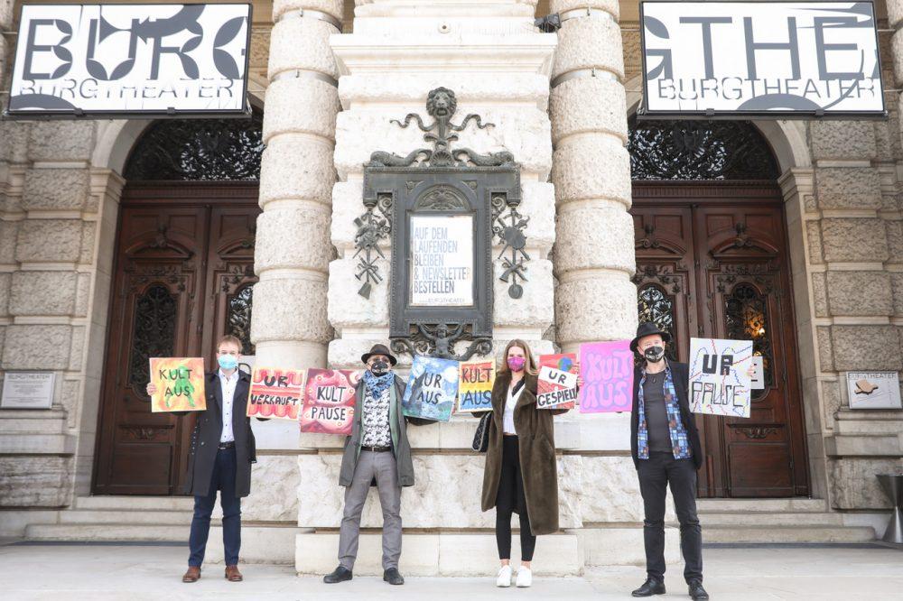 Vier Menschen vor dem geschlossenen Burgtheater. Sie halten Tafeln auf denen sie die Öffnung von Kunst und Kultur als erste nach dem Lockdown fordern