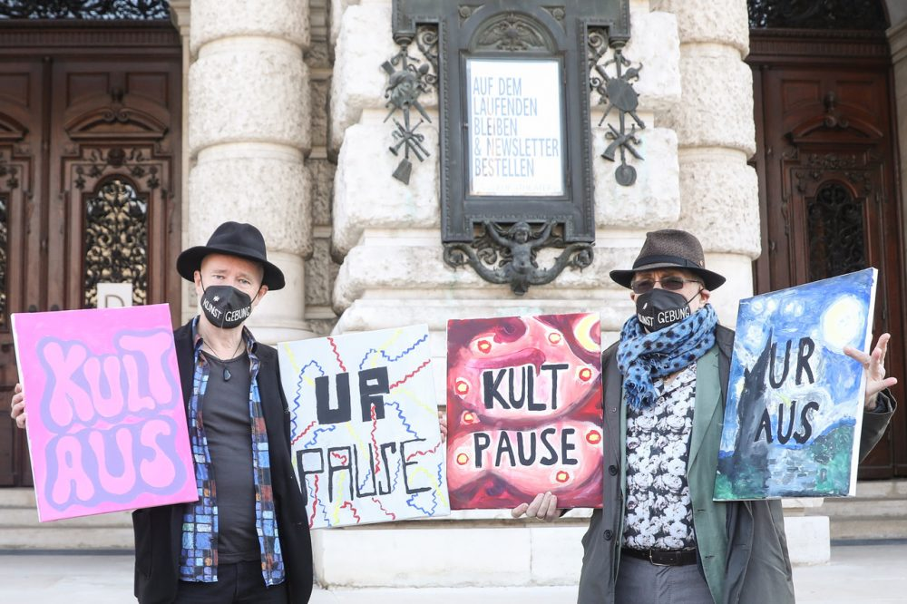 Zwei Männer vor dem geschlossenen Burgtheater. Sie halten Tafeln auf denen sie die Öffnung von Kunst und Kultur als erste nach dem Lockdown fordern