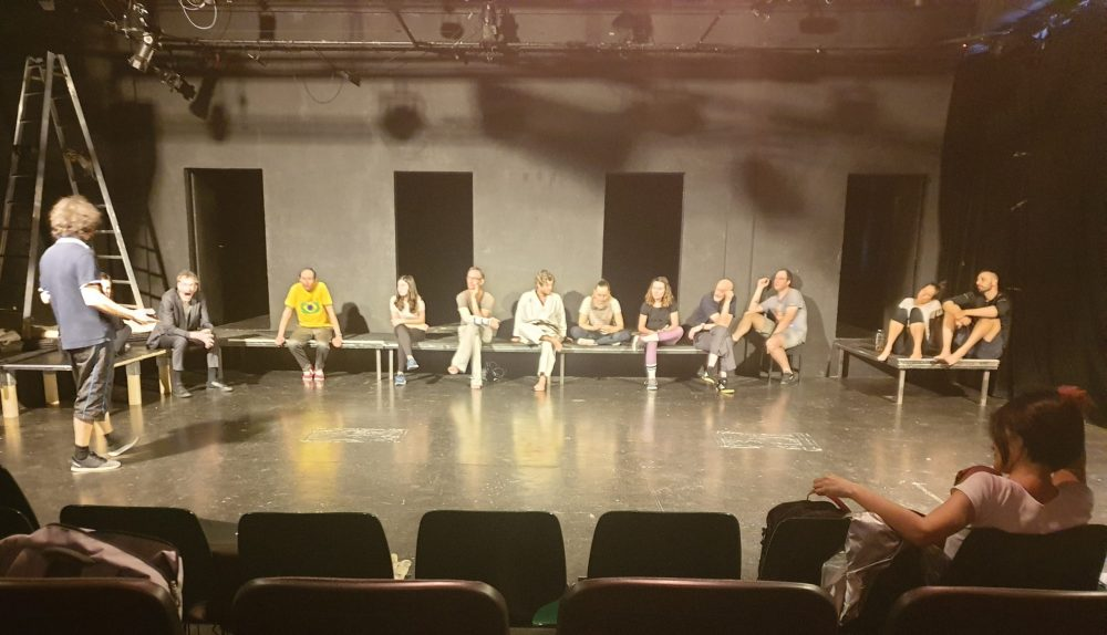 Schauspieler*innen sitzen auf einem Podest, Regisseur geht davor auf und ab