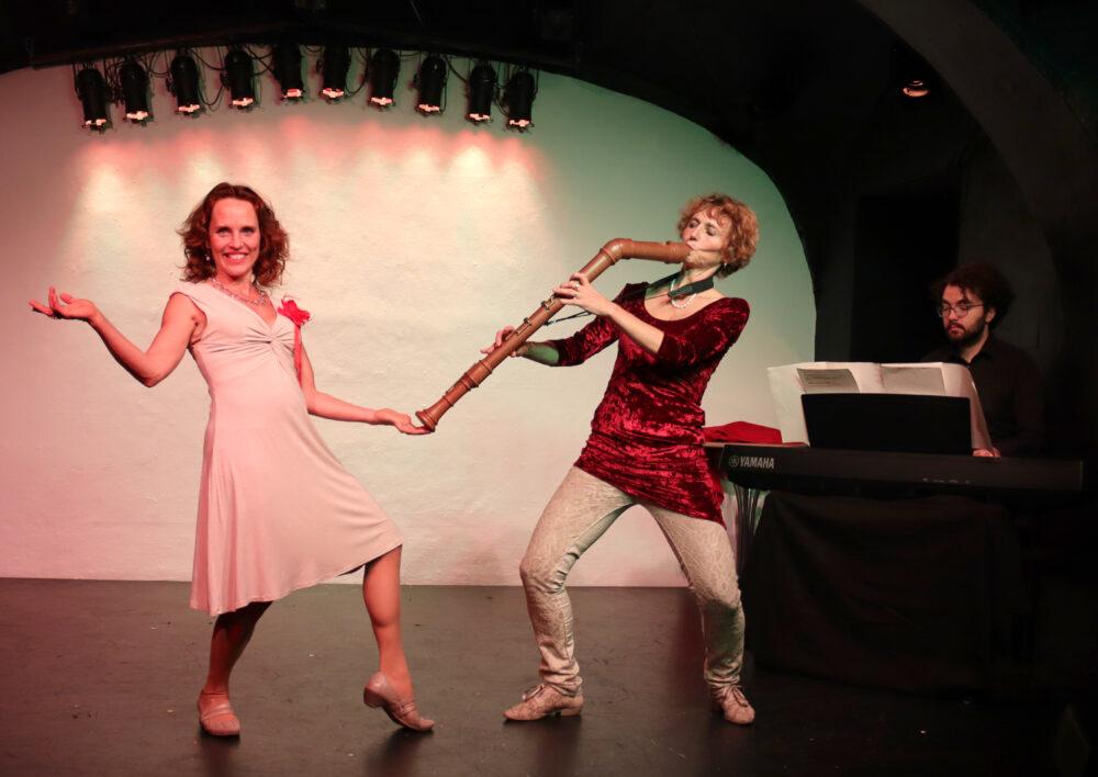 """Szenenfoto aus dem musikalischen Kabarettprogramm """"Zwa Goschn Oper"""" - zwei Frauen auf der Bühne, im Hintergrund ein Pianist"""