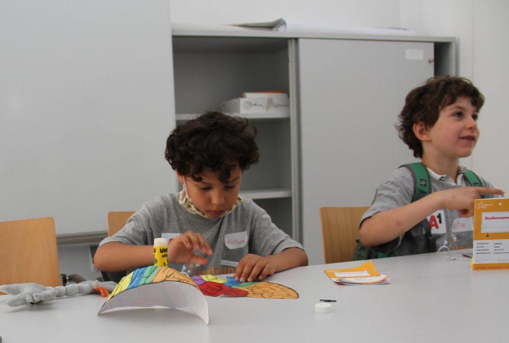 Kinder basteln aus Papierhälften ein buntes Gehirn