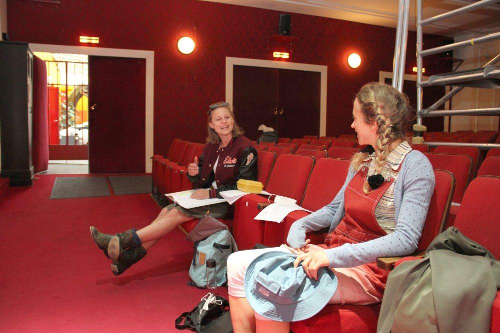 Zwei Schauspielerinnen, Viktoria Hauser und Runa Schymanski, auf einem Publikumssitzen
