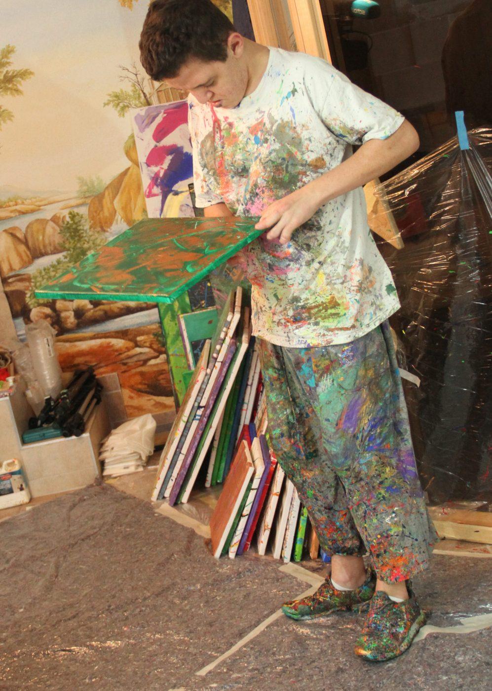 Jugendlicher schaut sein gemaltes bild an