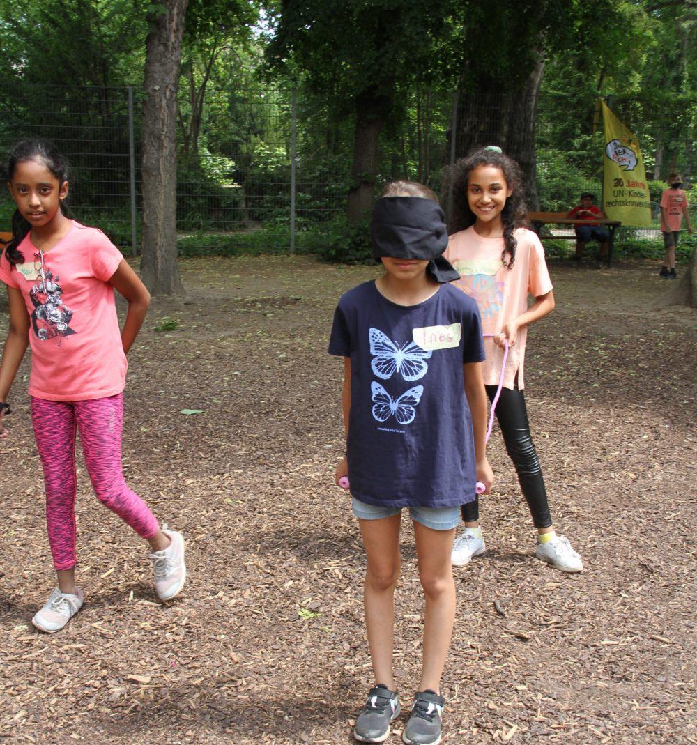 2er-Spiel: Dss vordere Kind mit verbundenen Augen hält die beiden Enden einer Schnur mit der das hintere Kind - mit offenen Augen - das vordere steuert und lenkt