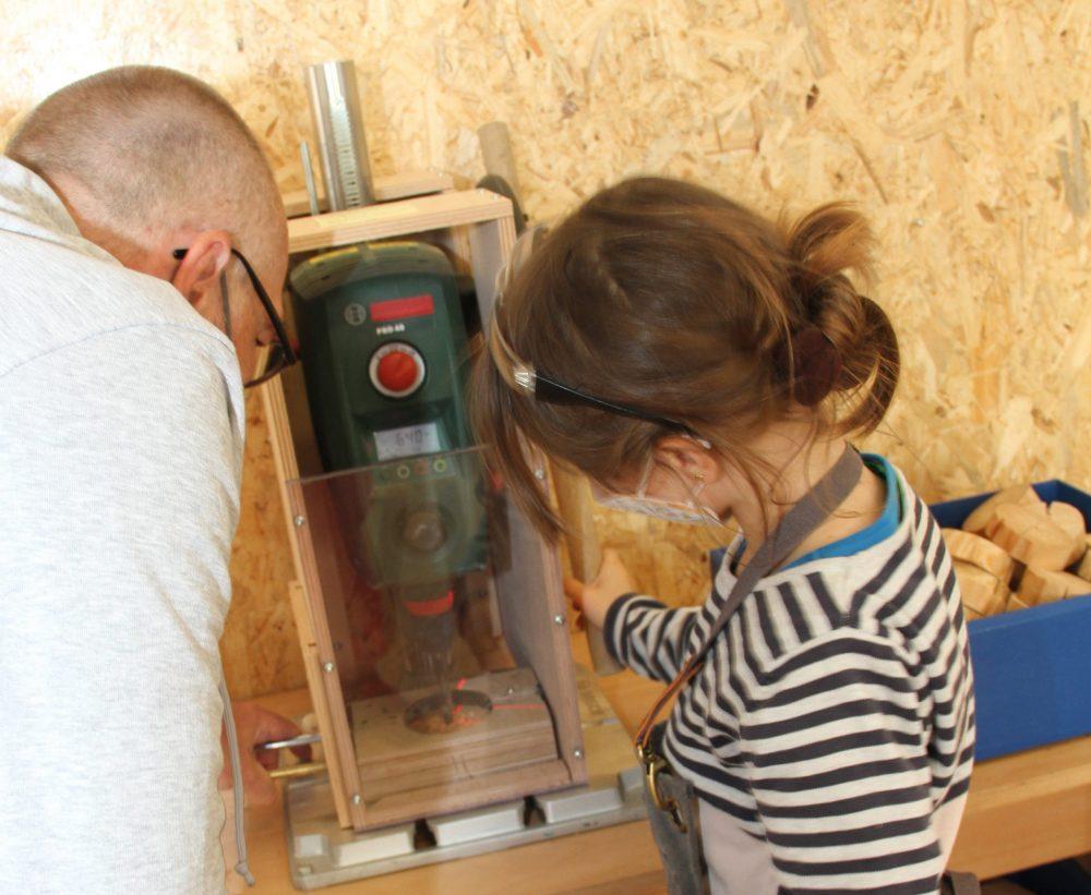 Mädchen bohrt mit Standbohrmaschine (schutz-ummantelt) Loch in runde Holz-Scheibe