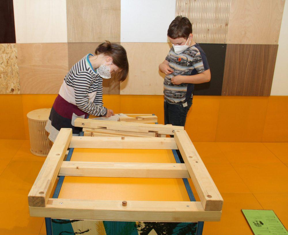 Kinder puzzlen das Modell eines Dachstuhls zusammen
