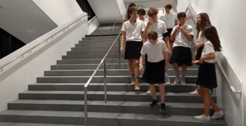 Auch Burschen gehen in Röcken einer Schuluniform die Stiegen des Schulhauses runter