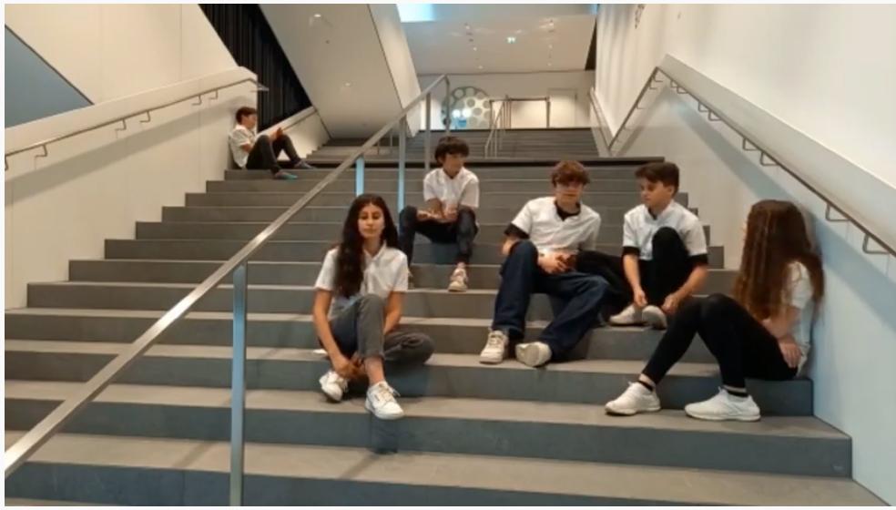 Jugendliche sitzen auf Stiegen im Schulhaus