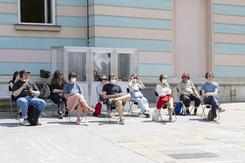 Zuhörer*innen auf Sesseln vor der Dolmetsch-Kabine