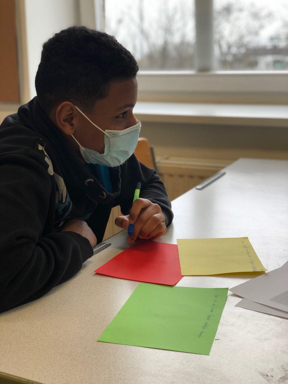 Jugedliche/r bereitet bunte Zettel für eine Plakatwadn vor