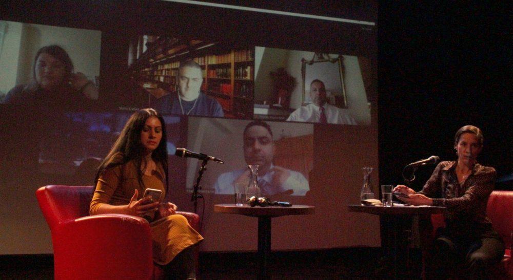 Diskussionsrunde auf der Bühne mit zugeschalteten Online-Gästen auf der Leinwand im Hintergrund