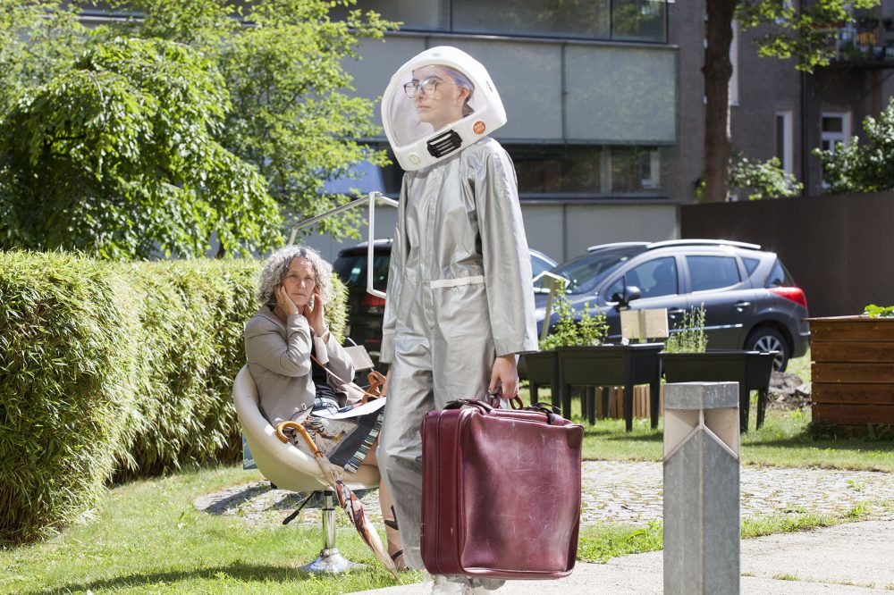 Schauspielerin in Raumanzug und mit Aktenkoffer quert den Weg vor einer Zuhörerin auf einem Erzählstuhl