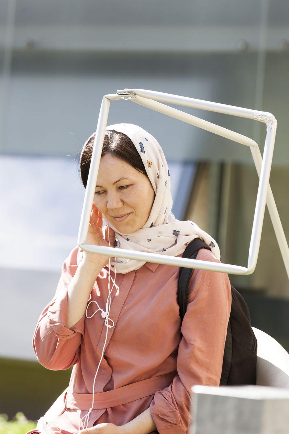Frau sittzt auf einem Stuhl, vor sich leere Bilderrahmen - eine der Stationen von