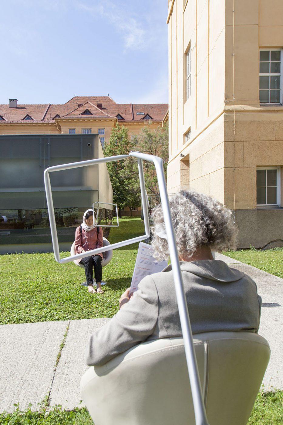 2 Frauen sitzen auf Stühlen, vor sich leere Bilderrahmen - eine der Stationen von