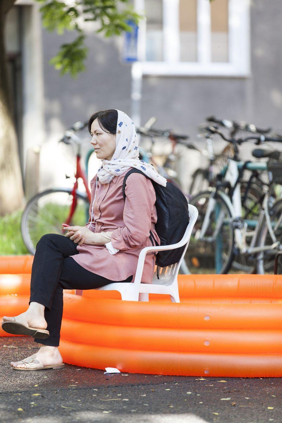 Zuhörer*innen auf Plastikstühlen in einem Kinderplanschbecken