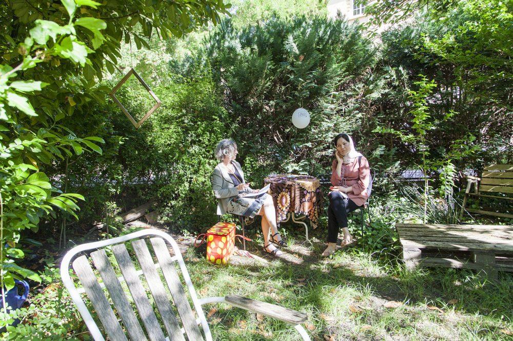Zuhörer*innen auf Erzählstühlen in einem Garten