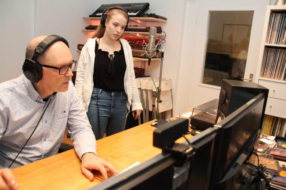 Junge Sängerin und Oroduzent an den Reglern im Tonstudio