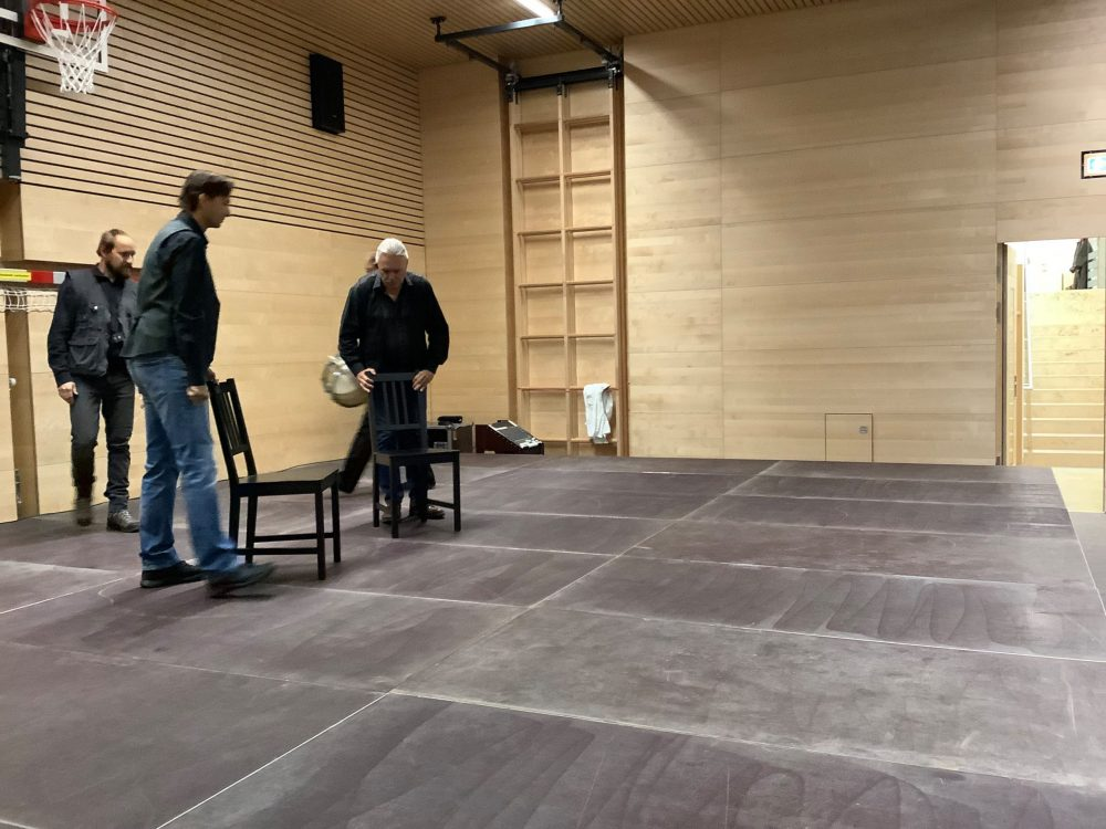Szenenfoto: Künstler kommen mit Stühlen auf die Bühne