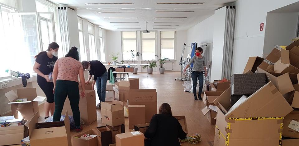Mitarbeiter*innen packen Sackerl in Kartons