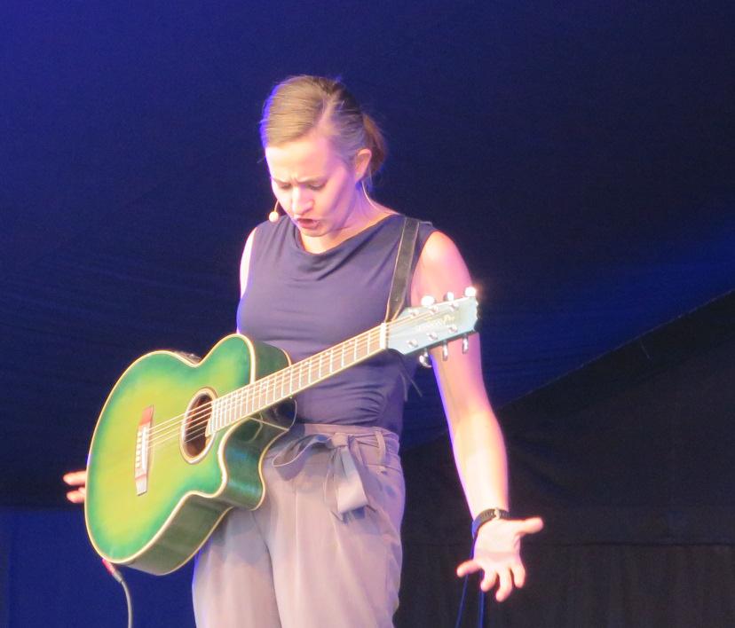 Kabarettistin Elli Bauer mit Gitarre auf der Bühne im Schwechater Felmayergarten