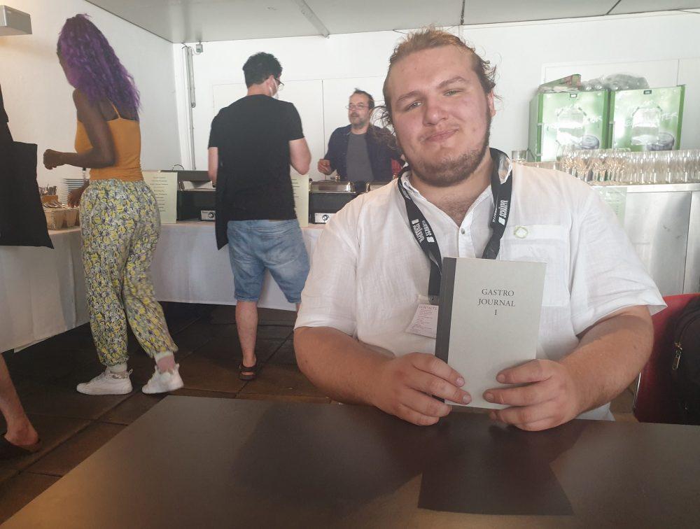 Jugendlicher mit einem Buch, in dem er selbst einen Beitrag veröffentlicht hat im Festival-Restaurant