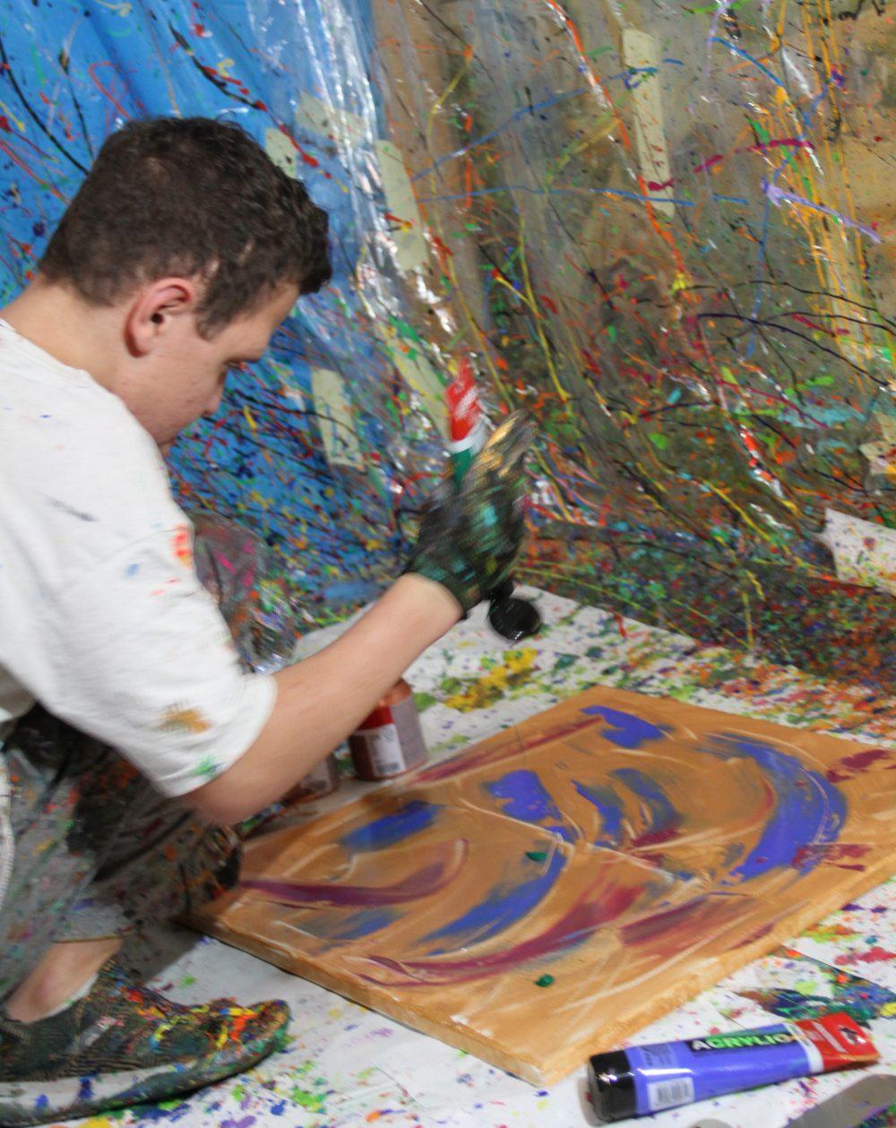 Jugendlicher spritzt Farben auf die am Boden liegende Leinwand
