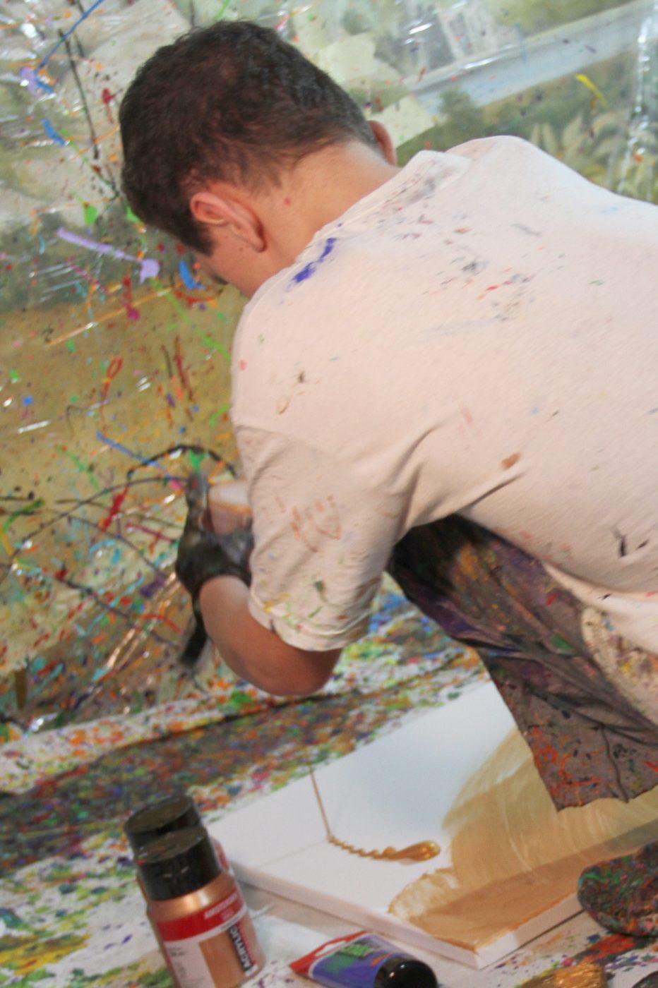 Jugendlicher spritzt Farben auf die auf dem Boden liegende Leinwand