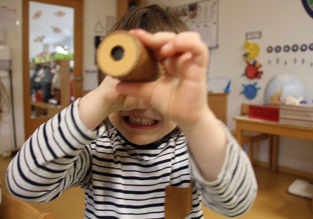 Kind schaut in ein Kaleidoskop, das ausschaut wie ein kleines Fernrohr