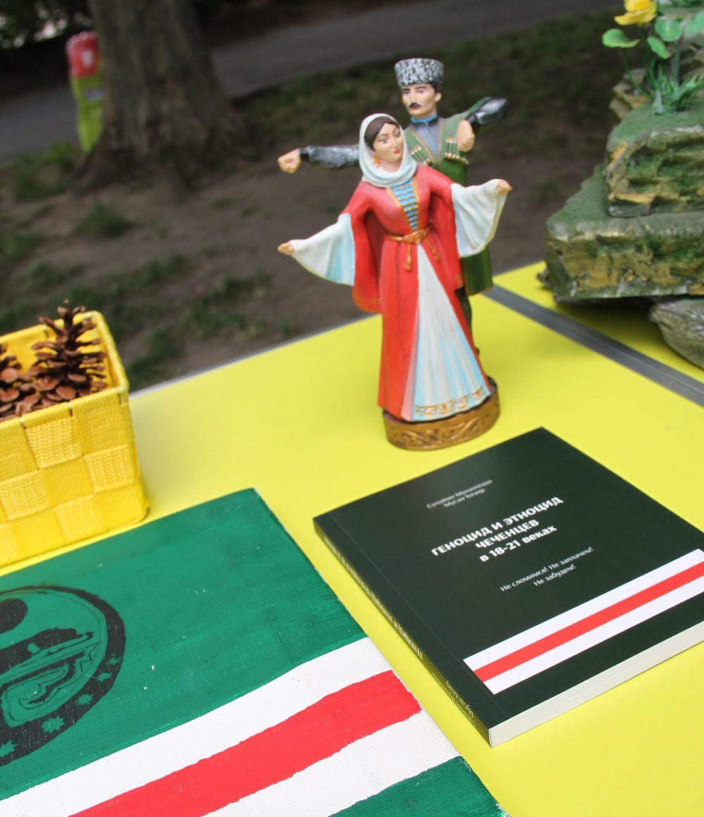 Tschetschnishe fahne, Figuren in Tracht und ein Buch