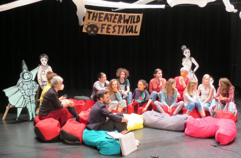 Kinder und Erwachsene sitzen im Halbkreis auf bunten Sitzsäcken auf der Bühne und diskutieren