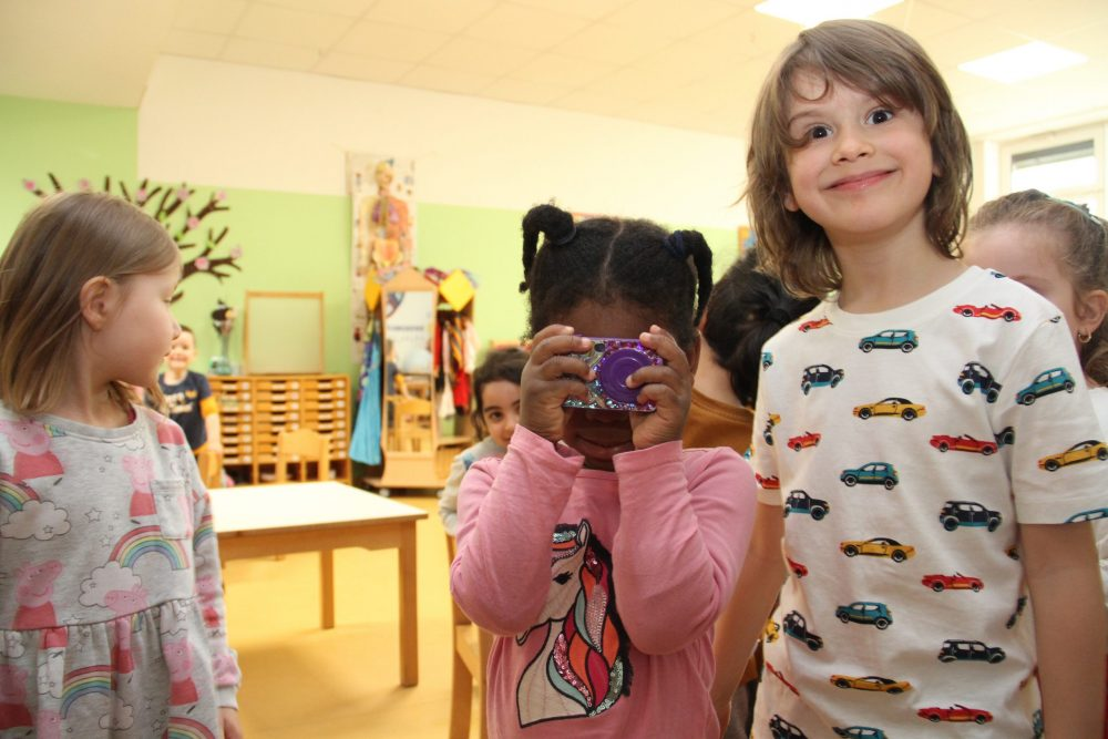 Kinder, eines hält eine Spielzeugkamera in die Kamera