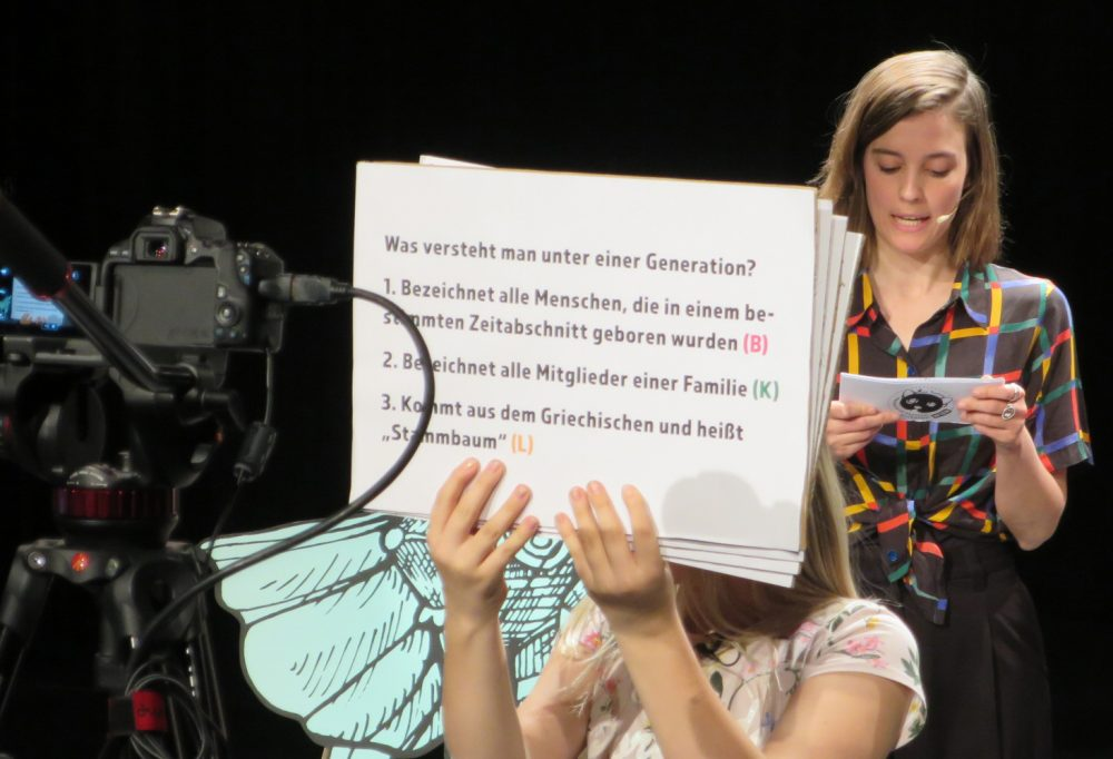 Ein Kind hält große Fragekarte in die Kamera