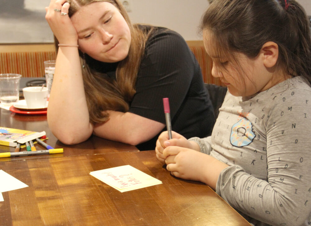 Kinder schreiben auf Zettel