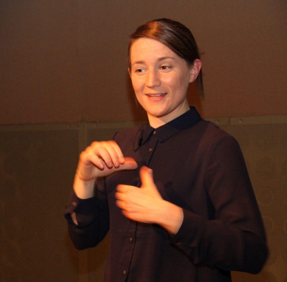 Gebärdendolmetscherin begrüßt das Publikum am Live-Stream