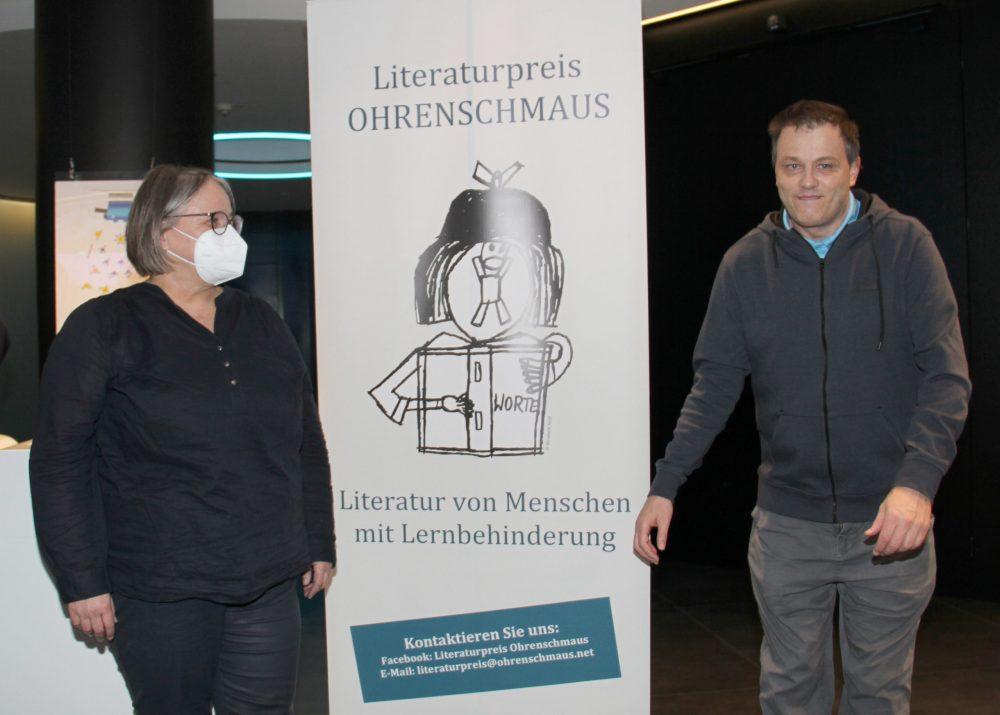 Hauptpreisträger Michael Wilhelm neben einem Plakat des Literaturpreises