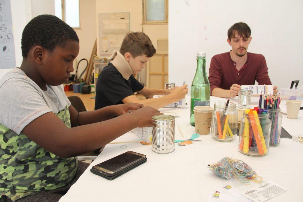 Kinder bauen aus einem Getränkekarton ein Saiteninstrument